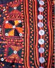 A close-up of the traditional pattern of a women's dress.  The buttons are hand-made of sea shells.