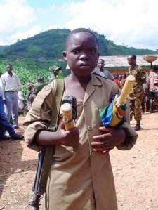 Rebel boy soldier with gun & umbrella, entering demobilization camp.  BINUB