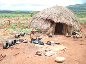 A Batwa home with pottery production in the front yard.  Women make the pots and men collect the clay