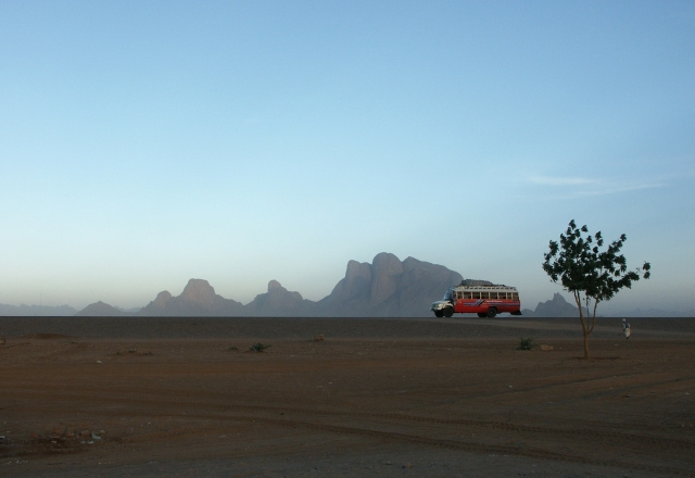 Desert bus to Kassala in the Red Sea Province - in the lower right corner of the picture a Beja can be seen walking towards the bus.  Source - (c) David Habarlah