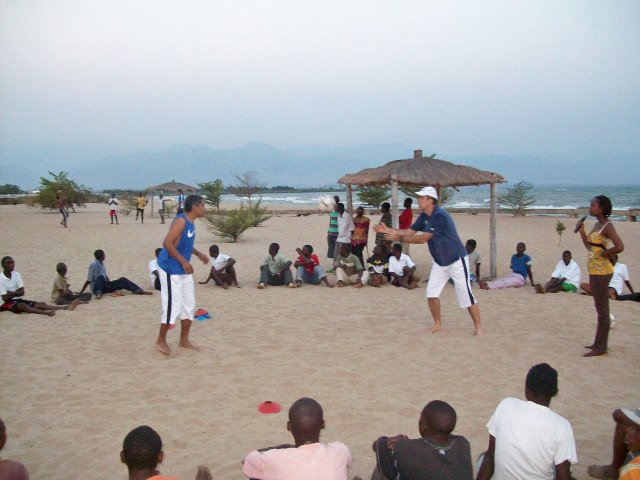 Demonstrating catches which were then practiced; another group is being trained in the background.  The woman on the right is Christella, who is translating from English to Kirundi for the coach.