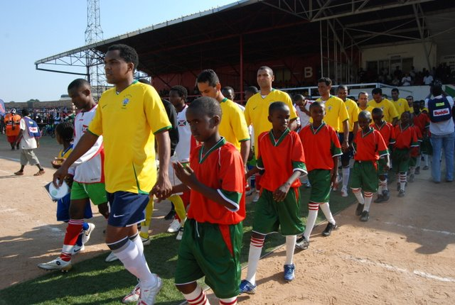 The Burundian national team & the Brazilian & Burundian teams entering the stadium, each with members of a youth team