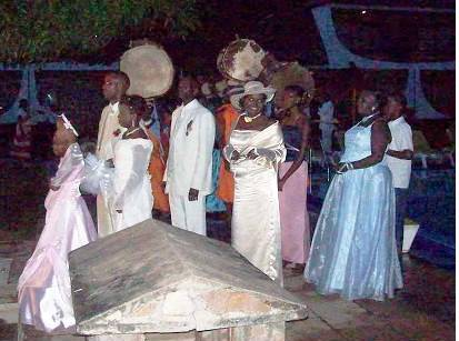 The couple mounts to the area where guests are seated, followed by traditional ntori drummers