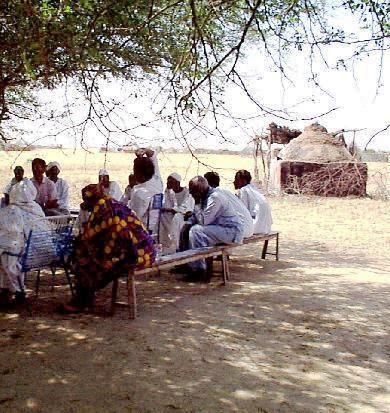 The village at the base of the Jebel was similar to this, and our socializing and meetings conducted in this style.  Source:  africanwaterorg-sudan.
