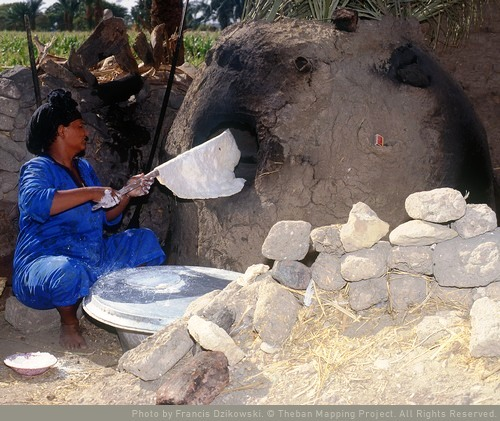 Woman placing ruqaq in oven.  Theban mapping project - Suzan Weeks
