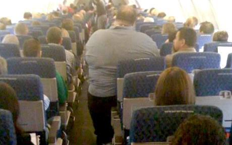 An obese man in economy class. Source: unknown