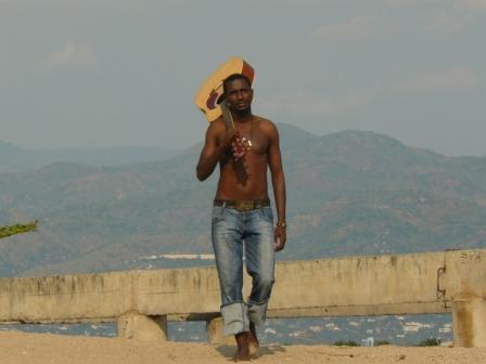 Steve Sogo on our beach with Bujumbura in the background.  Source: http://fidjomusic.com/steven-sogo.html