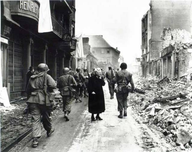 The US Seventh Army and a lost civilian moving through a German town.  Source - barewalls.com